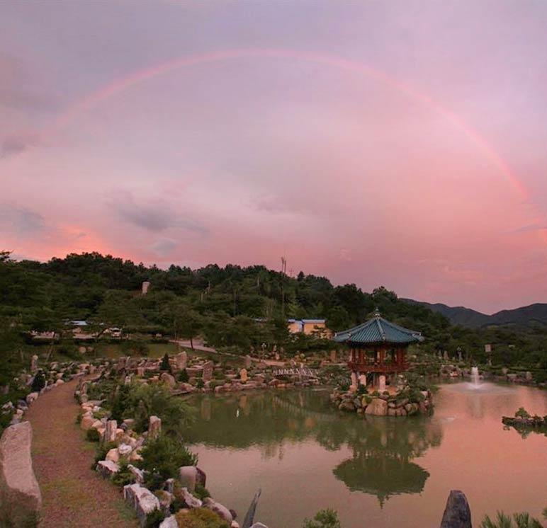 Rainbow arching over the Wolmyeongdong lake pavilion at dusk