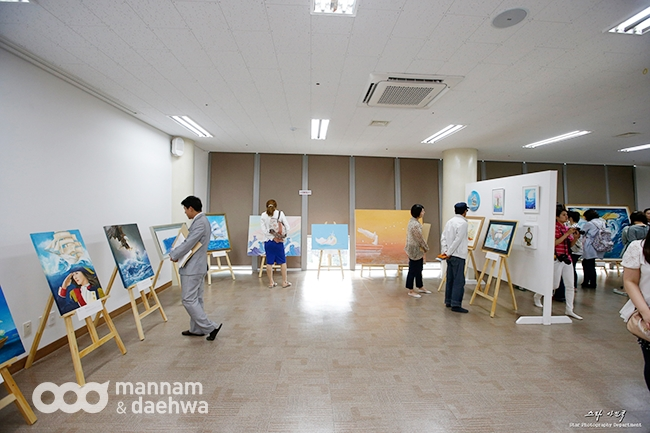People look through an art exhibition in Wolmyeongdong